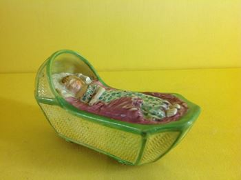 A pearlware model of a child in a cradle