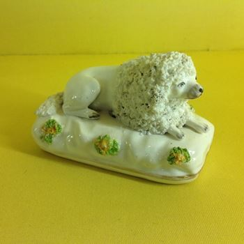 A Staffordshire model of a recumbent poodle