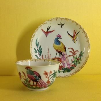 A Giles decorated Chinese porcelain tea bowl and saucer